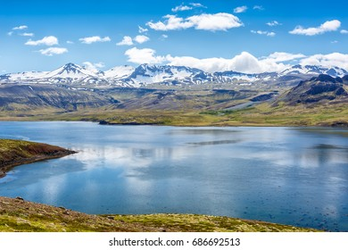 Icelandic lake on a background of mountains under cloudy sky
