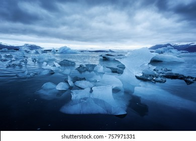 Icelandic landscape with blue icebergs in Jokulsarlon glacial lagoon. Large glacier on a foreground. Iceberg pieces in frozen lake. Vatnajokull National Park, southeast Iceland, Europe