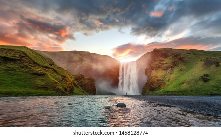 Icelandic Landscape. Classic long exposure view of famous Skogafoss waterfall with colorful sky during sunset. Skoga river, highlands of Iceland, Europe. Popular Travel destinations. Amazing nature