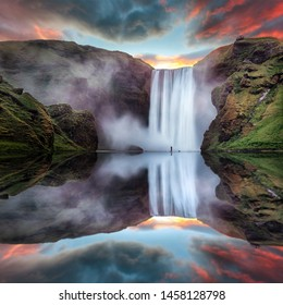 Icelandic Landscape. Classic long exposure view of famous Skogafoss waterfall with reflections. Dramatic Scenery of Iceland during sunset. majestic Skogafoss Waterfall in countryside with colorful sky