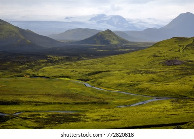 icelandic landscape with fog and hills with green moss and snowy mountains
