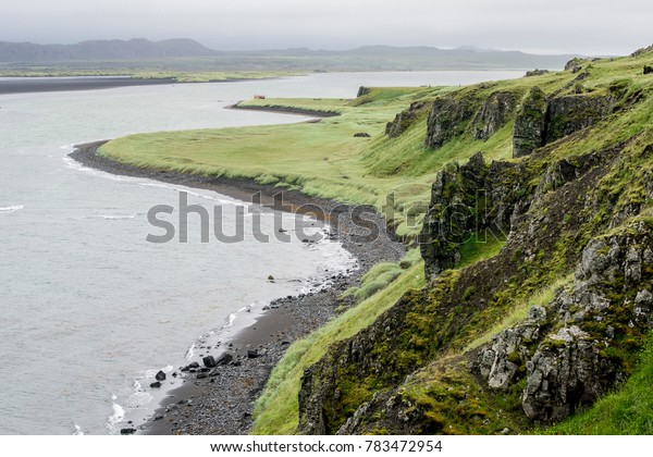 Icelandic shore near the Hvitserkur rock with a lot of rocks and grass