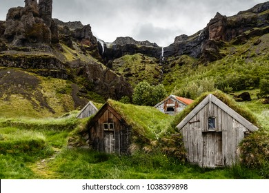 Icelandic turf houses and rocks with waterfall in the background near Kalfafell vilage, Southern Iceland