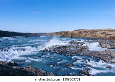 Icelandic waterfall with a rainbow and winter landscape in a beautiful sunny day against blue sky