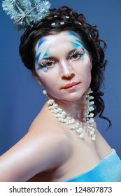 Ice-queen. Young woman in creative image with silver blue artistic make-up and perfect hairstyle.