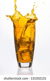 Ices cubes falling in a glass filled with orange liquid on white background