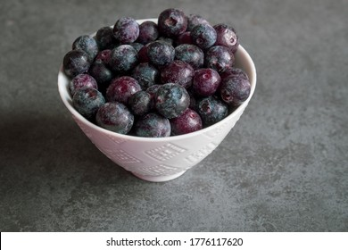 icey and frozen blueberries sit in a white bowl while still covered in frost