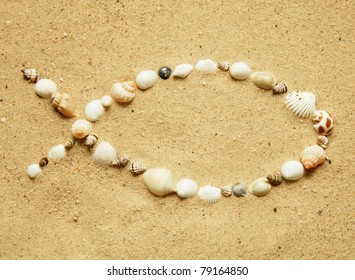 Ichthys, the Christian symbol of a fish, formed with small seashells on a smooth sandy beach