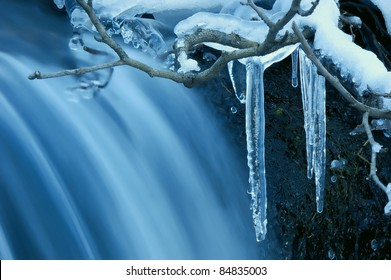 Icicle frozen on a branch of a tree near a mountain stream. The winter nature