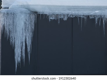 icicles draping from roof of exterior building on cold winters day in freezing temperatures bordering blank space for type