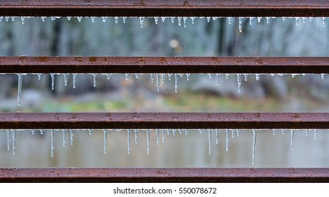 Icicles hang from horizontal, rusted, iron bars in fence covered in thick ice from a winter ice storm