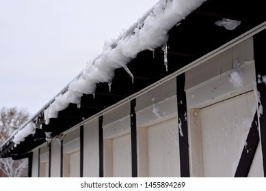 Icicles hang on the edge of a shuttered with selective focus and blurred depth.