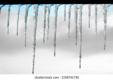 Icicles hang on the roof of a house against a bright blue sky. Spring landscape with icicles hanging from the roof of the house. Set of snow icicles, snow hat.