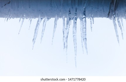 Icicles hang on the roof of a village house over bright blue sky background