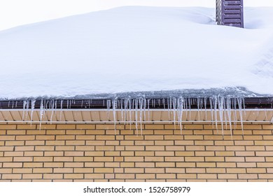 Icicles. Icicles hang on the roofs of house in winter. Winter, icicles, ice on the roof. Long icicles on background of snow.