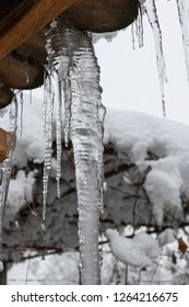 Icicles hang from roof eaves, melting. Danger of falling ice and snow from the eaves of buildings