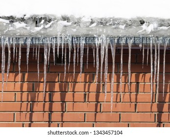 Icicles hang from the roof of a red brick house, outside in sunny weather in spring