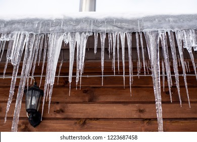 Icicles hang from the roof of a wooden house in the countryside, on a frosty cloudy day.