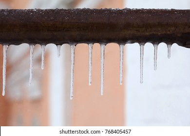 Icicles hanging from a brown pipe. Frozen water and metal surface, winter time concept. selective focus shallow depth of field photo.