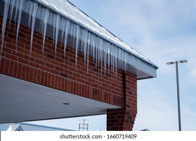 Icicles are hanging and dripping from a commercial building because spring weather is finally coming!