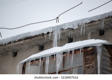 Icicles hanging from  house..Large icicles hanging from the roof.