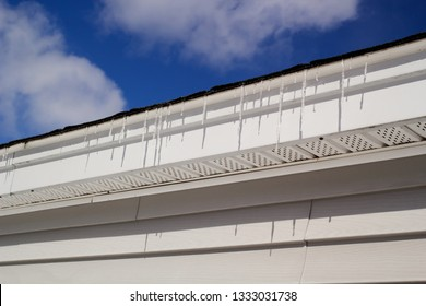 Icicles hanging off house roof.