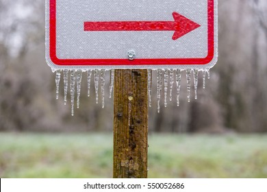 Icicles hanging from a right pointing, red directional arrow on a  sign covered in ice