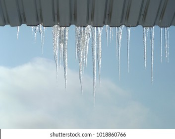 icicles hanging from the roof, against the sky