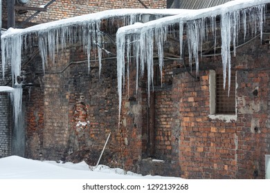 Icicles hanging from roof of the building/ old house, dangerous situation, сold winter, severe winter, poor thermal insulation, ice stalactite, formation of icicles, frost and winter weather concept.