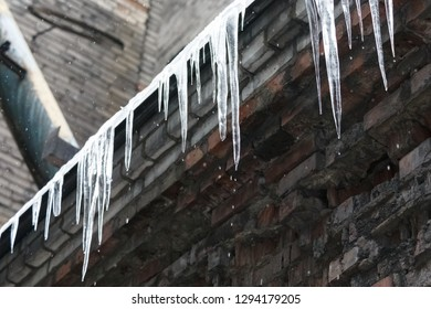 Icicles hanging from roof of the building, water drips from them/ fall icicles, sudden warming, сold winter, poor thermal insulation, ice stalactite, formation of icicles, winter weather concept.