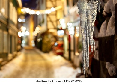 Icicles hanging in a small street in the German Eifel village of Monschau during christmas time at night. Focus on the icicles, Germany.