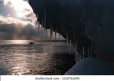 Icicles on a cave off the coast of estonia. A cold feeling comes from the dripping ice next to the sea. A low warm sun in winter.