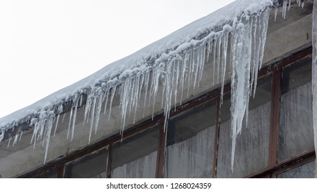 Icicles on the drainpipe and ditch. Incorrect installation of the drainage system, on which large icicles appear that pose a threat to the health and lives of people passing by.