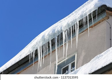icicles on the rain pipe of a building