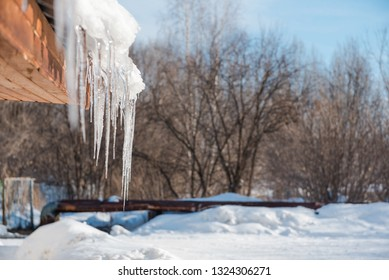 Icicles on the roof. Melt the snow on the roof of the house. Caution icicles. Ice hanging from the roof of the house. Icicles