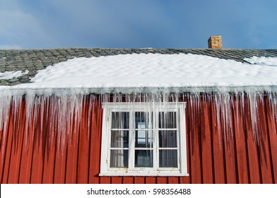 icicles on the roof of a red house in Norway. melting icicles. natural ice formation in winter time.