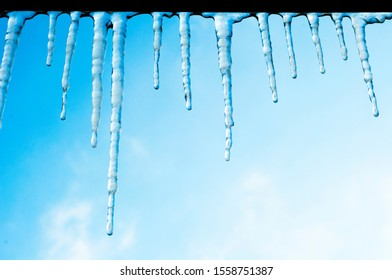 Icicles in the roof of a house against a bright blue sky. Spring-winter landscape with icy, transparent, shiny icicles on a clear sunny day in winter.