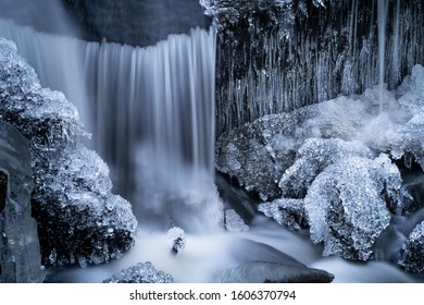 Icicles in a small waterfall in a forest creek.