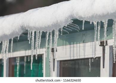 Icicles and snow hanging from a gutter in freezing winter conditions in England during the beast from the east storm. Garden shed close up of frozen water.