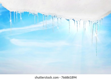 Icicles in spring against bright blue sunny sky
