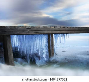 Icicles under wooden jetty in frozen lake on cold winter day