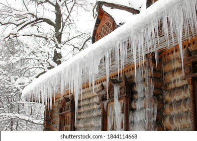 Icicles in winter. The old hut is covered with ice in winter. Icicles hang from the roof. The wooden tower is covered with ice. Icicles hang on the roof of a house. The logs of the hut were frozen