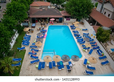 Icmeler, Turkey - 9th June 2019: View from hotel balcony overlooking Private hotels relaxing pool area with sun loungers, umbrellas, blue pool and floatation inflatables.