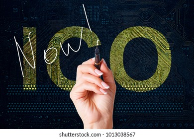 ICO procedure Initial coin offering poster. The female hand is writing the word now on the PC circuit board.
