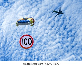 ICO sign is flying on a parachute from an airplane. Airdrop token. Giveaway.