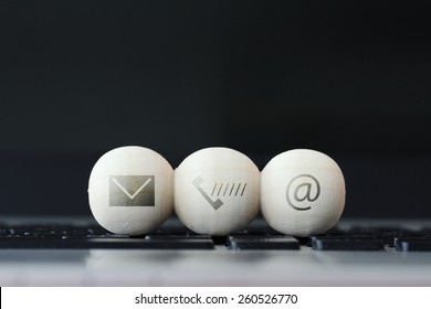 icon on wooden ball of website and internet contact us page concept on computer laptop  keyboard