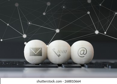 icon on wooden ball of website and internet contact us page concept on computer laptop keyboard and social media diagram