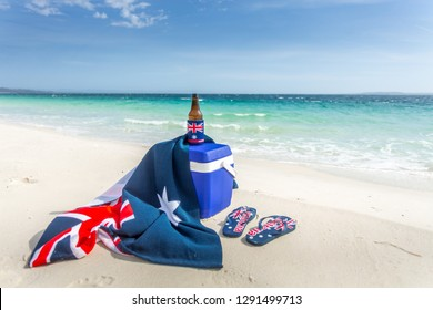 Iconic Australian items on a beach, esky, beach towel, beer or beverage and thongs.  Some items have the Australian flag on them