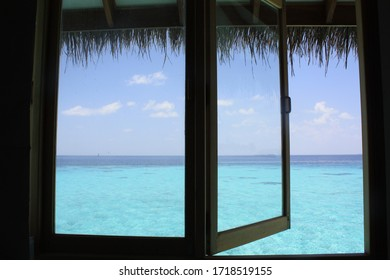 Iconic and beautiful view from an overwater bungalow on the turquoise blue water of a lagoon in the Indian ocean in Maldives island.