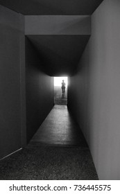 Iconic black and white picture of dark narrow corridor with individual silhouette escaping in the light